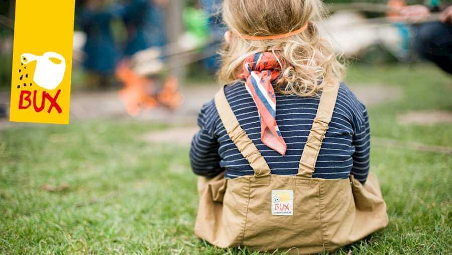Kind sitzt mit der BUX Regenhose im Matsch