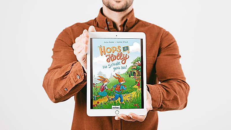Papa hält das iPad mit dem Titelbild des eBooks Hoos und Holly - Die Schule geht los