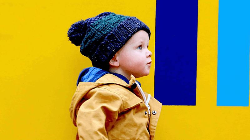 Junge spaziert mit kuscheliger Mütze und Regenjacke im Herbst