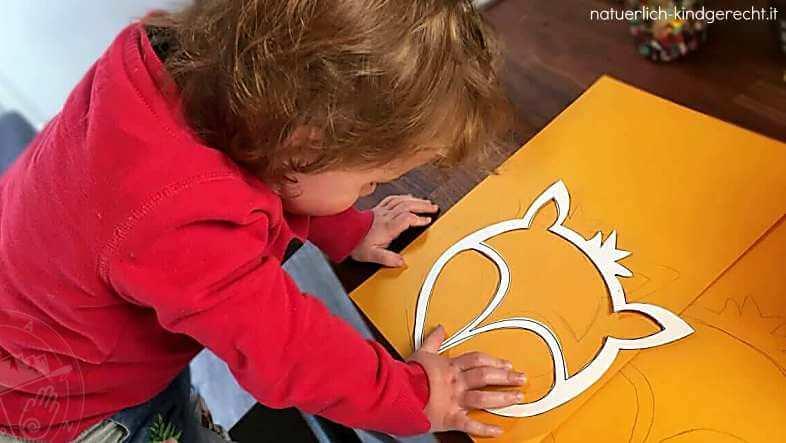 Mädchen paust die Vorlage für die Fuchslaterne auf orangefarbenen Karton
