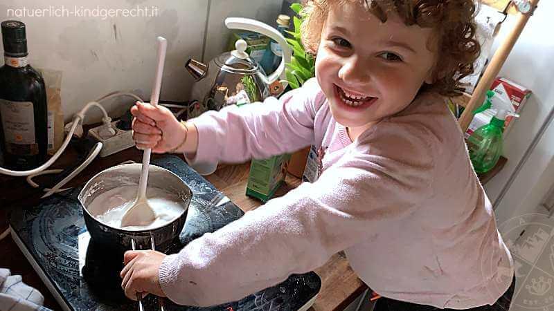 Mädchen kocht auf dem Herd Kaltporzellan und eigene Knete